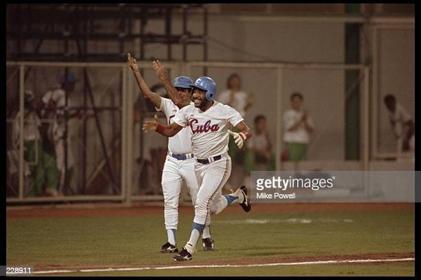 Victor Mesa of Cuba celebrates as he rounds third base after hitting a homerun during Cuba's 61 victory over the USA at the 1992 Summer Olympics in...