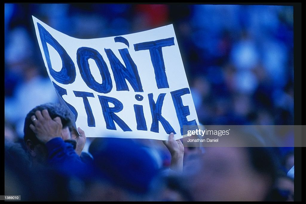 Fans hold up signs in protest of the baseball strike during a game between the San Diego Padres and the Chicago Cubs at Wrigley Field in Chicago...