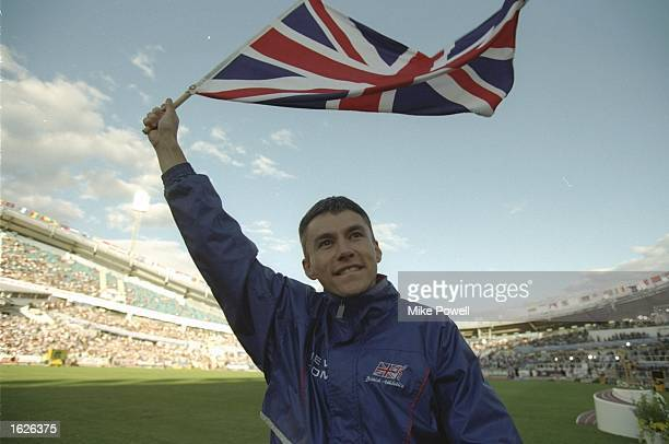 Jonathan Edwards of Great Britain celebrates with the national flag after setting a new World Record in the Triple Jump event with a jump of 1829...