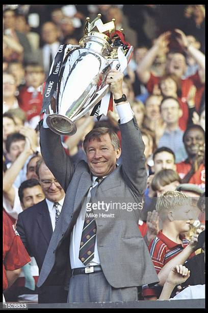 Alex Ferguson of Manchester United holds aloft the Premier league trophy before the start of the preseason friendly between Manchester United and...