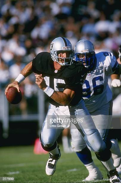 Quarterback Jeff Hostetler of the Oakland Raiders is chased out of the pocket by defensive lineman Cotez Kennedy of the Seattle Seahawks during a...