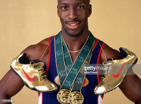 Sprinter Michael Johnson poses for a studio portrait with his two Olympic gold medals and his golden running shoes Johnson became the first man to...