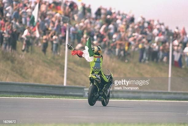 Valentino Rossi of Italy waves the Italian National flag from his Aprilia after winning the 125cc class of the Czech Grand Prix at the Brno circuit...