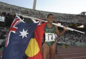 Cathy Freeman of Australia carries the national and Aboriginal flags after winning the gold medal in the 400 metres final during the World...