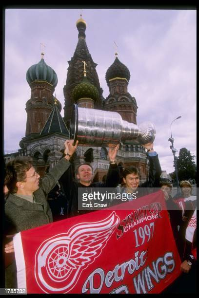 Defenseman Viacheslav Fetisov center Igor Larionov and Vyacheslav Kozlov of the Detroit Red Wings carry the Stanley Cup at Red Square in Moscow...