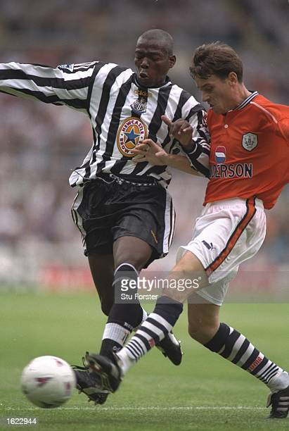 Faustino Asprilla of Newcastle United wins the ball ahead of Ian Nolan of Sheffield Wednesday during the Premier League match at St James Park in...