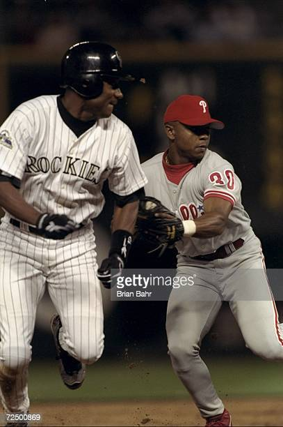 Desi Relaford of the Philadelphia Phillies attempts to tag Darryl Hamilton of the Colorado Rockies out during a game at Coors Field in Denver...