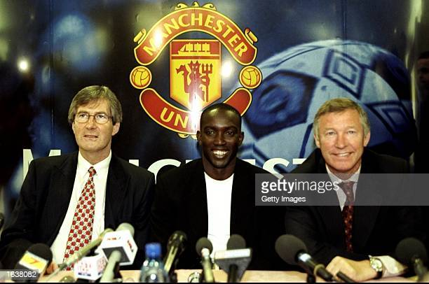 Dwight Yorke of Trinidad and Tobago is welcomed by chairman Martin Edwards and manager Alex Ferguson after completing his 12 million pound transfer...