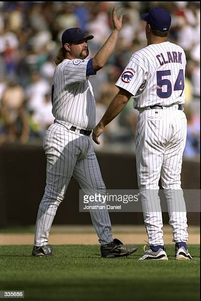 Pitcher Rod Beck of the Chicago Cubs is congratulated by teammate Mark Clark during a game against the San Francisco Giants at Wrigley Field in...