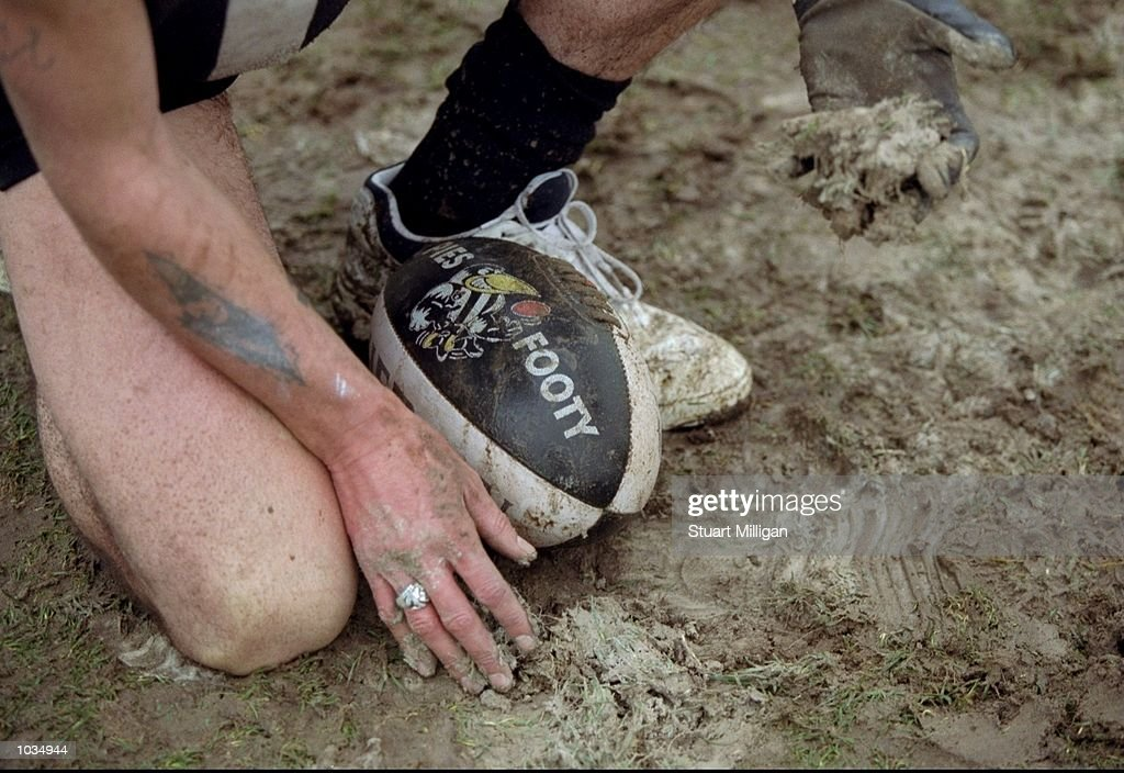 A Collingwood supporter collects mud at Victoria Park in Collingwood Victoria Australia following the AFL Round 22 game against Brisbane The Lions...