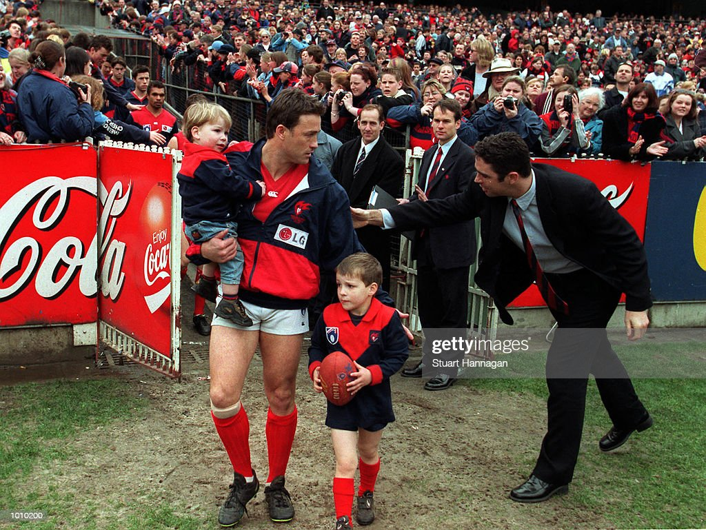 Melbourne captain Todd Viney with his children is congratulated by former captain Garry Lyon as he runs out for his last game with his team before the AFL round 22 game Melbourne v Essendon at the MCG.Essendon defeated Melbourne. MandatoryCredit: Stuart Hannagan/ALLSPORT