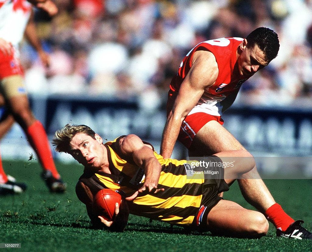 Shane Crawford,#9 for Hawthorn handballs clear of Jared Crouch,#28 for the Sydney Swans, during the round 22 Australian Football League match between Hawthorn and Sydney played at Waverley Park, Melbourne, Australia. Hawthorn defeated Sydney by eighty five points. Mandatory Credit: Stuart Milligan/ALLSPORT