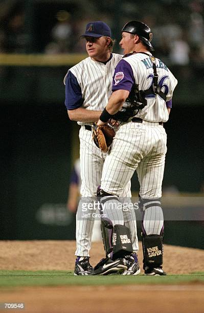 Pitcher Curt Schilling of the Arizona Diamondbacks talks with Catcher Damian Miller at the mound during the game against the Atlanta Braves at Bank...