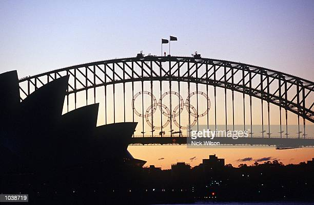 Sunset over the Olympic Rings on the Sydney Harbour Bridge and the Opera House as the Olympic Games loom on Sydney Harbour Sydney Australia Mandatory...