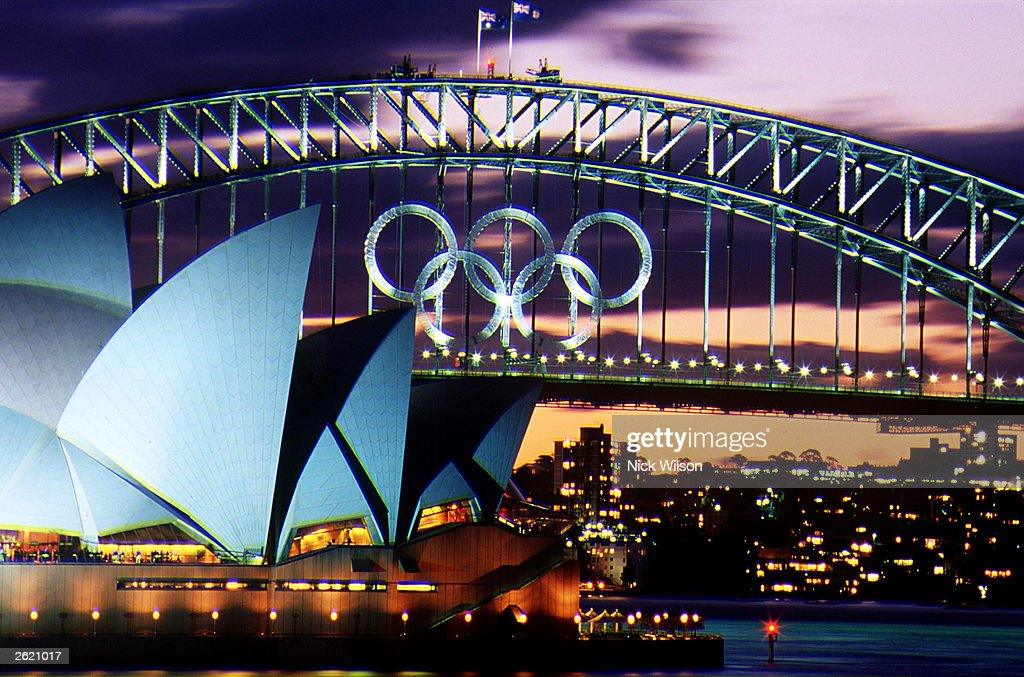 Sunset over the Olympic Rings on the Sydney Harbour Bridge and the Opera House as the Olympic Games loom on Sydney Harbour Sydney Australia October...