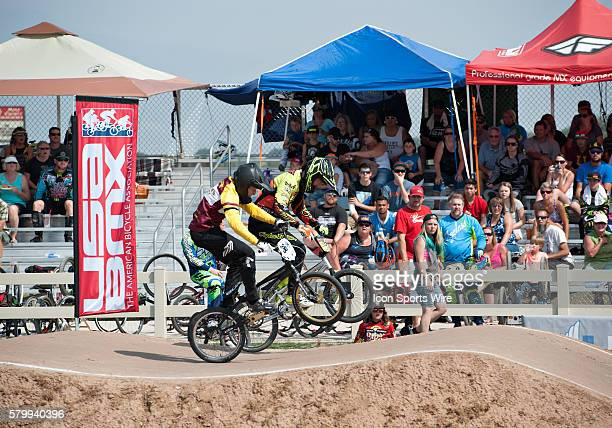 Pedal to the Medal's Larry Huff battles Colorado Clothing Company's Derrik Blackmore toward the finish line during USA BMX's Mile High Nationals at...