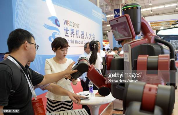 BEIJING Aug 23 2017 Visitors watch a robot during the World Robot Conference 2017 in Beijing capital of China Aug 23 2017 The fiveday robot...