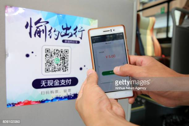 A passenger pays for bus ticket by quick response code in Beibei District southwest China's Chongqing Municipality Aug 3 2017 Mobile payments started...