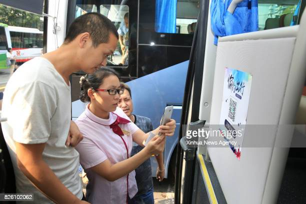 A staff member explains how to pay for bus ticket by quick response code in Beibei District southwest China's Chongqing Municipality Aug 3 2017...