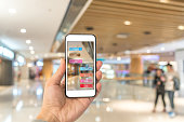 Augmented reality marketing in the shopping mall. Hand holding smart phone use AR application to check information