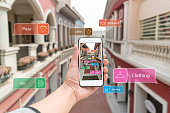 Augmented reality marketing street. Hand holding smart phone use AR application to check information