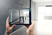 Man's hands holding a digital tablet with the augmented reality app which shows the table and the chair in the new empty office.