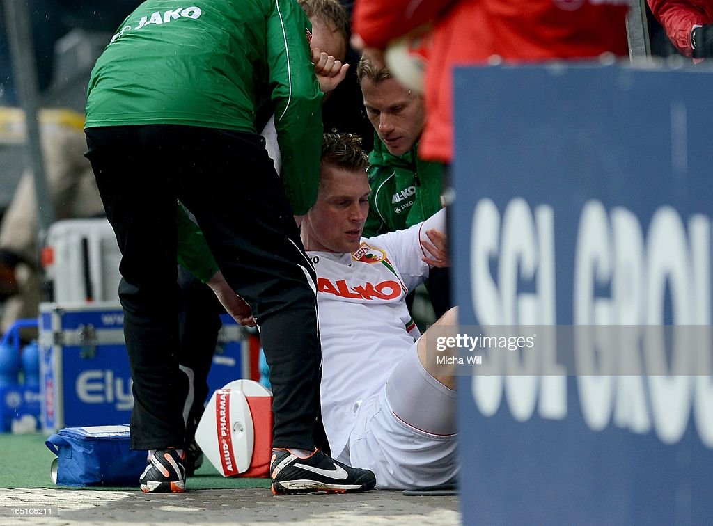 FC Augsburg coaching staff assist <a gi-track='captionPersonalityLinkClicked' href=/galleries/search?phrase=Jan-Ingwer+Callsen-Bracker&family=editorial&specificpeople=758385 ng-click='$event.stopPropagation()'>Jan-Ingwer Callsen-Bracker</a> of Augsburg after he he collided with advertising hoardings during the Bundesliga match between FC Augsburg and Hannover 96 at SGL Arena on March 30, 2013 in Augsburg, Germany.