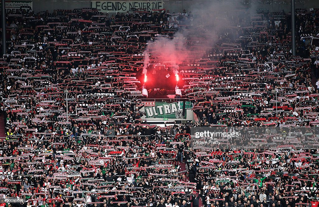 Augsburg fans in the grandstand mourn the loss of some Augsburg fans before the Bundesliga match between FC Augsburg and 1899 Hoffenheim at WWKArena...