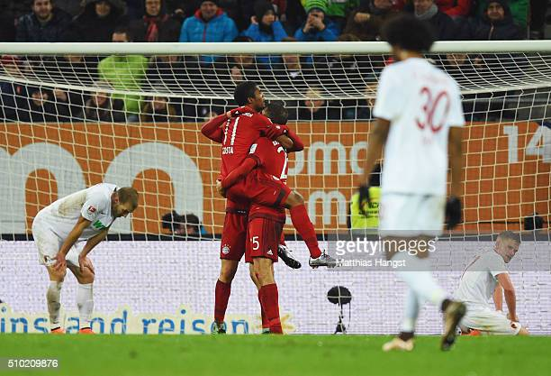 Augsburg players look dejected as Thomas Mueller of Bayern Munich celebrates with Robert Lewandowski and Douglas Costa as he scores their third goal...