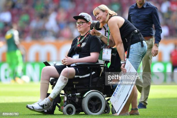 Augsburg supporter Simon who sits in a wheelchair following an accident and his mother Marion ahead of the Bundesliga match between FC Augsburg and...