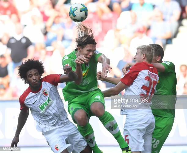 Augsburg's Brazilian midfielder Caiuby Moenchengladbach's Danish defender Jannik Vestergaard Augsburg's Austrian defender Martin Hinteregger and...