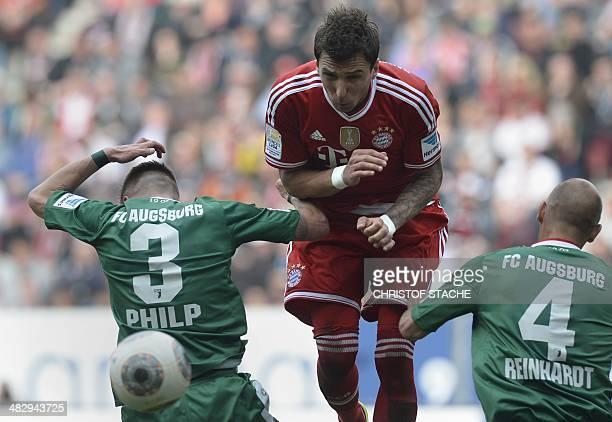 Augsburg's defender Ronny Philp Bayern Munich's Croatian striker Mario Mandzukic and Augsburg's defender Dominik Reinhardt vie for the ball during...