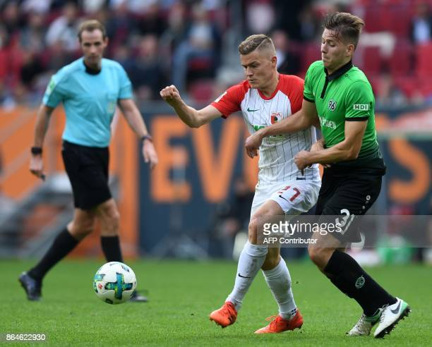 Augsburg's Icelandic forward Alfred Finnbogason and Hanover's midfielder Waldemar Anton vie for the ball during the German first division Bundesliga...