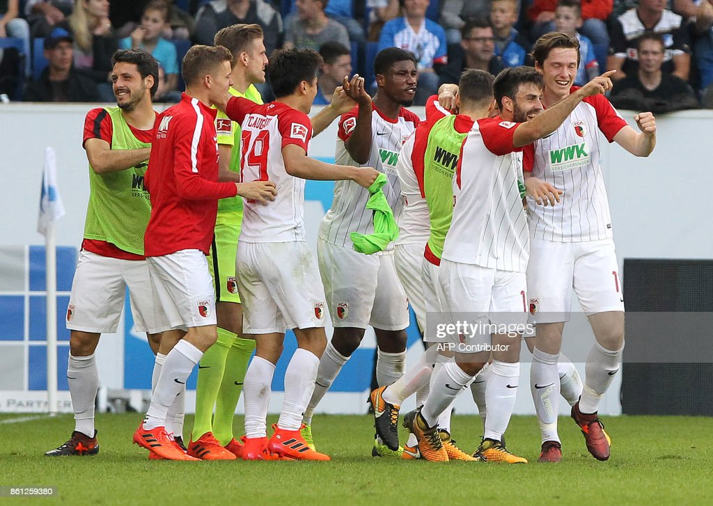 Augsburg's players celebrate after scoring the 2-2 during the German First division Bundesliga football match TSG 1899 Hoffenheim vs FC Augsburg in Sinsheim, southwestern Germany, on October 14, 2017. / AFP PHOTO / Amelie