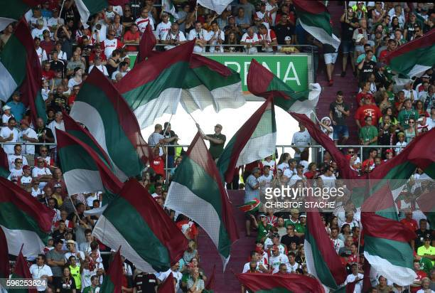 Augsburg's supporters wave with flags ahead the German first division Bundesliga football match of FC Augsburg vs VfL Wolfsburg in Augsburg southern...
