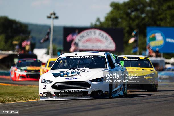 NASCAR Sprint Cup Series driver Brad Keselowski driver of the Miller Lite Ford leads the field through the bus stop after a late race caution during...