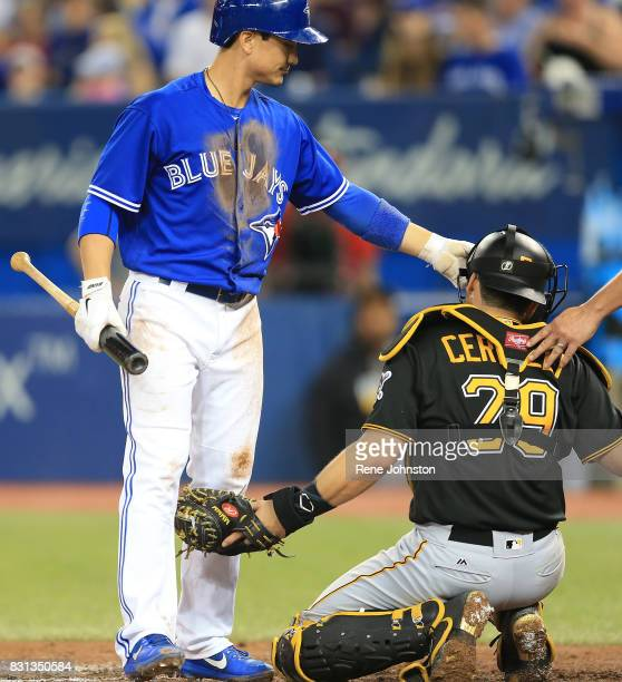 TORONTO ON August 12 Toronto Blue Jays Darwin Barney fixes the mask of Pittsburgh Pirates catcher Francisco Cervelli after a tip ball moved his mask...