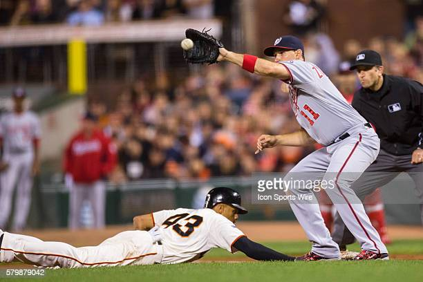 San Francisco Giants right fielder Justin Maxwell dives back to first base just before Washington Nationals first baseman Ryan Zimmerman makes the...