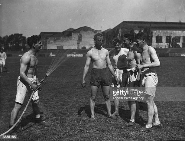 The players of Queens Park Rangers Football Club enjoy an outdoor shower after a training session