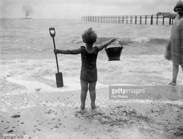 A little boy waves his bucket and spade at the waves as he watches the sea on the beach at ClactononSea