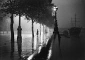 A man standing alone on a raindrenched pavement on the River Thames Embankment London