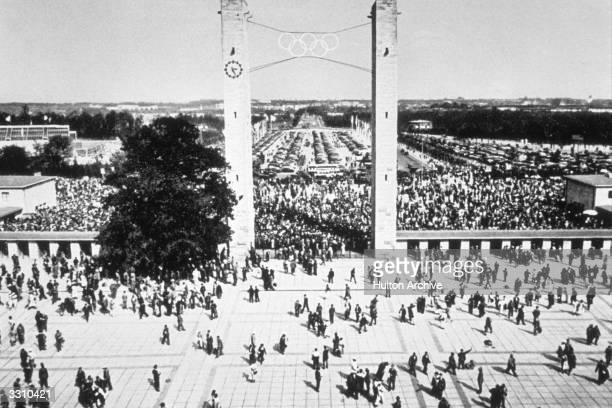 Crowds streaming through the east gate of Berlin's Olympic stadium to watch Adolf Hitler officially open the 1936 games
