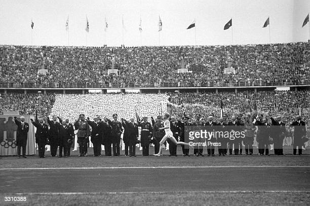 The Olympic torch is carried into the Berlin stadium at the start of the 1936 Olympic Games