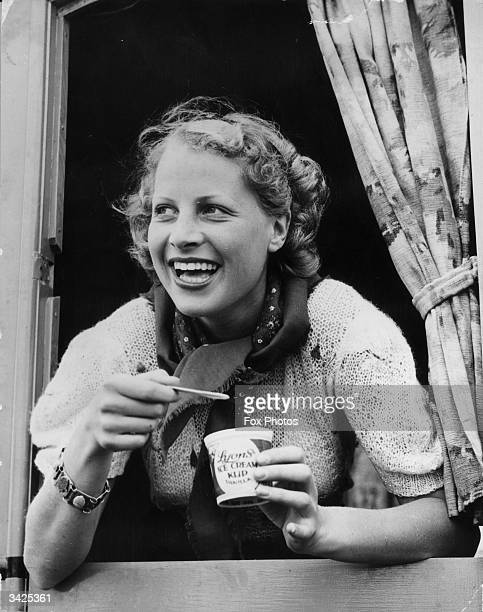 A woman leans from a window to eat a tub of Lyons Ice Cream Kup as part of an advertising campaign