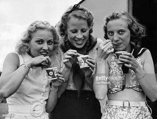 Three young women enjoy tubs of icecream