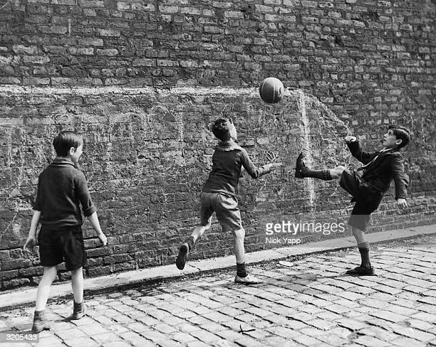 A group of boys playing football in the street in Salford Lancashire