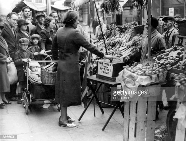 A shopper at London's Lambeth Walk's market contributes to the spitfire fund