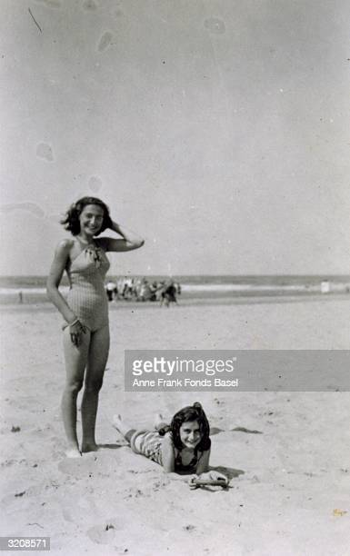 EXCLUSIVE Portrait of Margot Frank standing and her sister Anne Frank lying on a beach taken from Anne's photo album Zandvoort