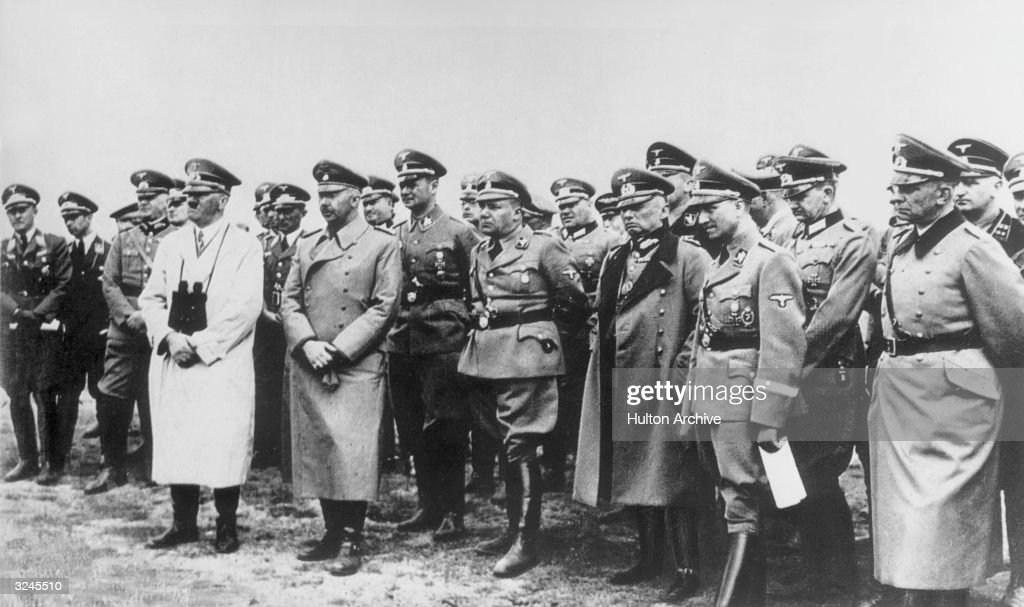 Nazi leader Adolf Hitler stands with Heinrich Himmler and his staff contemplating the chances of an invasion while looking across the English Channel...