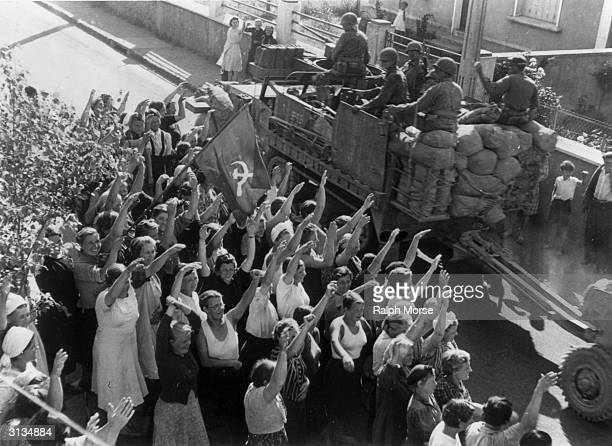 Some of the 215 Russian women captured by the Germans nearly four years before in Leningrad and taken to France as slave labourers wave a homemade...